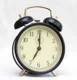Reloj de alarma en el fondo blanco Fotos de archivo libres de regalías