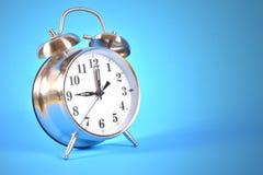 Reloj de alarma en fondo azul Imagen de archivo
