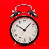 Reloj de alarma en rojo Foto de archivo libre de regalías