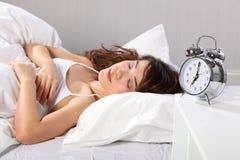 Reloj de alarma hermoso el dormir de la mujer a las siete Imagen de archivo libre de regalías