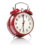 Reloj de alarma rojo del viejo estilo aislado en blanco Imagen de archivo libre de regalías