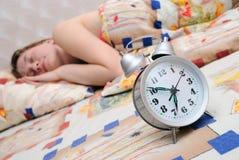 Reloj de alarma sobre dormir la muchacha Fotografía de archivo libre de regalías