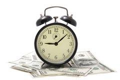 Reloj de alarma sobre el montón del dinero aislado Fotos de archivo