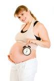 Reloj de alarma sonriente de la explotación agrícola de la mujer embarazada Imágenes de archivo libres de regalías