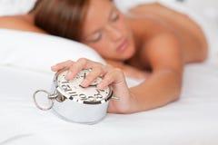 Reloj de alarma y el dormir de la explotación agrícola de la mujer Imágenes de archivo libres de regalías