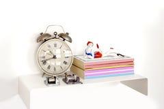 Reloj de alarma y libros Imagen de archivo libre de regalías