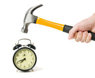 Reloj de alarma y mano con el martillo Fotos de archivo