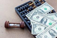 Reloj de arena con el ábaco y el billete de banco fotografía de archivo libre de regalías
