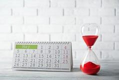 Reloj de arena con el calendario fotografía de archivo