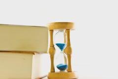 Reloj de arena con el libro fotografía de archivo libre de regalías