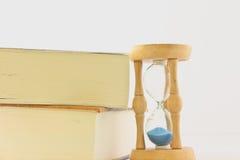 Reloj de arena con el libro fotografía de archivo