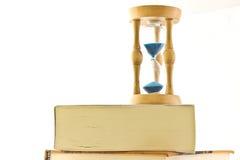 Reloj de arena con el libro imagen de archivo