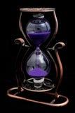 Reloj de arena con la arena púrpura en un marco metálico imagen de archivo