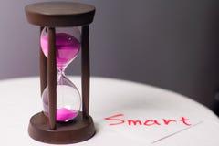 Reloj de arena con la arena rosada fotos de archivo