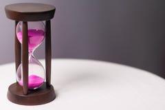 Reloj de arena con la arena rosada imagen de archivo