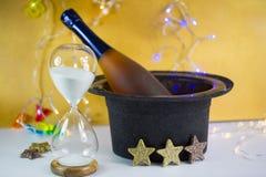 Reloj de arena con la botella del champán en el cilindro - ` s Eve del Año Nuevo Fotografía de archivo