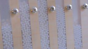 Reloj de arena con las pequeñas bolas blancas almacen de video