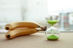 Reloj de arena con los plátanos en el fondo, primer fotos de archivo libres de regalías