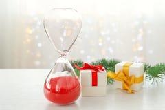 Reloj de arena con los regalos y la decoración en la tabla cuenta de +EPS los días 'hasta la pizarra de la Navidad Imagen de archivo