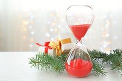 Reloj de arena con los regalos y la decoración en la tabla cuenta de +EPS los días 'hasta la pizarra de la Navidad Foto de archivo libre de regalías
