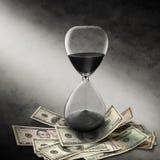Reloj de arena del dinero del tiempo del asunto Imagenes de archivo