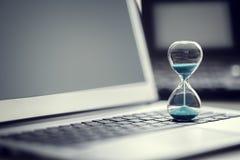 Reloj de arena en el concepto del ordenador portátil para la gestión de tiempo fotografía de archivo libre de regalías