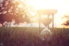 Reloj de arena en el tiempo de la hierba durante puesta del sol Estilo de la vendimia Imagen de archivo libre de regalías