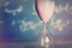 Reloj de arena en la madera con un fondo de la pizarra Foto de archivo libre de regalías