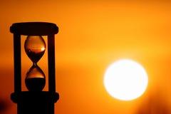Reloj de arena en puesta del sol Foto de archivo libre de regalías