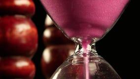 Reloj de arena en soporte de madera Arena rosada Cierre para arriba almacen de video