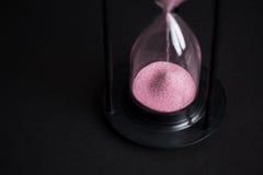 Reloj de arena negro grande contra un fondo negro Imágenes de archivo libres de regalías