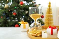 Reloj de arena, regalos y decoración festiva en la tabla cuenta de +EPS los días 'hasta la pizarra de la Navidad Foto de archivo libre de regalías