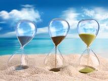 Reloj de arena tres en la arena Imágenes de archivo libres de regalías