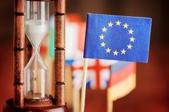 Reloj de arena y bandera de la unión europea El tiempo se está ejecutando hacia fuera Imagenes de archivo
