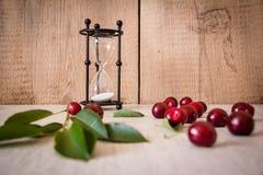 Reloj de arena y cerezas en la tabla Fotos de archivo libres de regalías