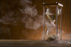 Reloj de arena y humo en una tabla de madera Imágenes de archivo libres de regalías
