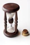 Reloj de arena y monedas Fotografía de archivo