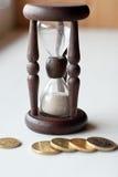Reloj de arena y monedas Fotos de archivo