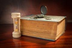 Reloj de arena y reloj con el libro antiguo Fotos de archivo libres de regalías
