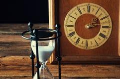 Reloj de arena y reloj viejo del vintage Imagenes de archivo
