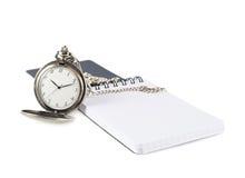Reloj de bolsillo al lado de un cuaderno Foto de archivo libre de regalías