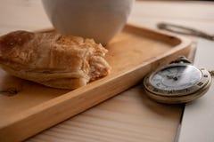 Reloj de bolsillo antiguo del oro colocado en el lado de la bandeja de madera con una taza del caf? con leche y la empanada se ha imagenes de archivo