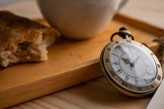 Reloj de bolsillo antiguo del oro colocado en el lado de la bandeja de madera con una taza del caf? con leche y la empanada se ha fotografía de archivo
