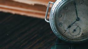 Reloj de bolsillo antiguo del vintage en el fondo de libros viejos metrajes