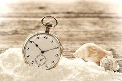 Reloj de bolsillo antiguo en arena en tarjetas de madera envejecidas Fotos de archivo