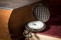 Reloj de bolsillo con el libro antiguo Imágenes de archivo libres de regalías