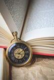 Reloj de bolsillo con los libros viejos en el papel arrugado en tono del vintage Imágenes de archivo libres de regalías