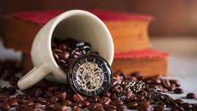 Reloj de bolsillo del lapso de tiempo y taza de café en la semilla del café y el libro viejo en la tabla de madera almacen de metraje de vídeo