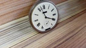 Reloj de bolsillo en el fondo de una pared de madera almacen de metraje de vídeo