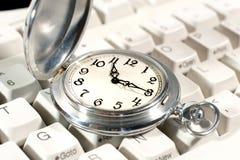 Reloj de bolsillo en el teclado fotografía de archivo